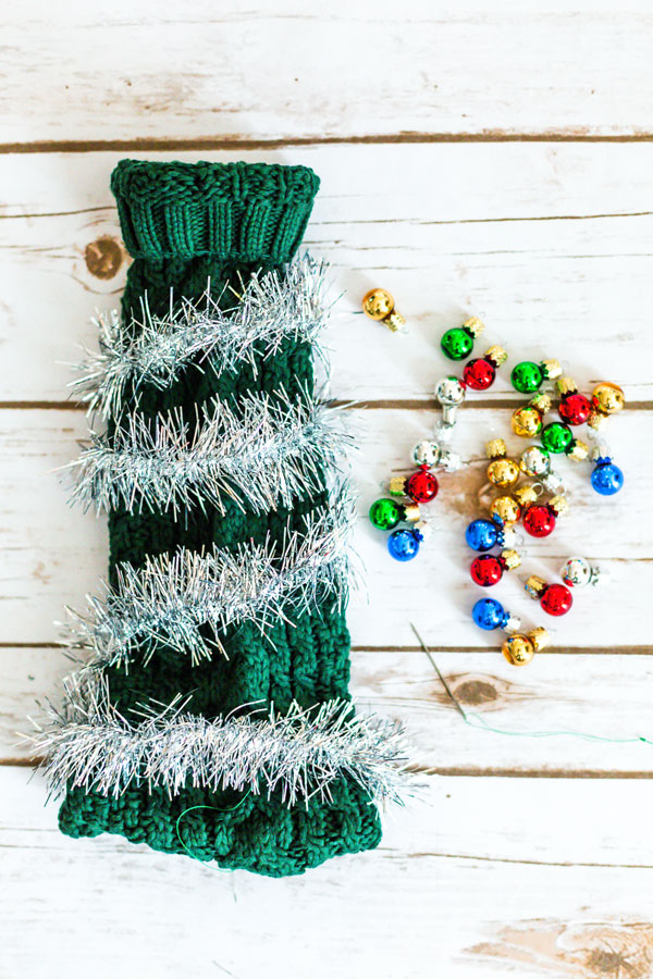 Heading to a fun, festive holiday party this year? Give the gift of a bottle of wine and dress it up with this Ugly Christmas Sweater for a Wine Bottle DIY.